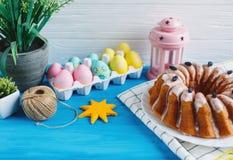 有蛋糕和手画五颜六色的鸡蛋的大板材,在蓝色背景的毛巾 关闭 装饰复活节 免版税库存图片