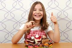 有蛋糕和赞许的小女孩 库存照片