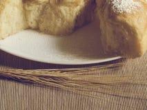 有蛋糕和麦子耳朵的板材 免版税库存图片