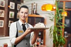 有蛋糕的女服务员女孩在餐馆的牌照 免版税库存图片