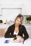 有蛋糕的妇女在厨房里 免版税图库摄影