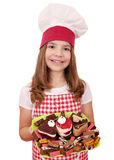有蛋糕的小女孩厨师 库存图片
