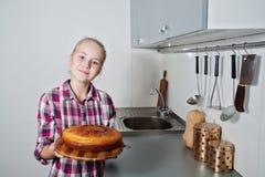 有蛋糕的美丽的女孩在厨房里 免版税库存照片