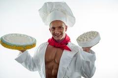 有蛋糕的年轻英俊的厨师 免版税库存图片