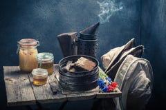 有蜂窝、帽子和蜂蜜的生锈的蜂农工具 免版税库存图片