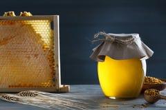 有蜂窝和花粉的蜂蜜瓶子 免版税库存图片