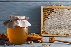 有蜂窝和花粉的蜂蜜瓶子 免版税图库摄影
