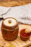 有蜂蜜里面的一个小小桶和在一张木桌上的一把匙子 纬向条花 土气的生活仍然 免版税库存图片