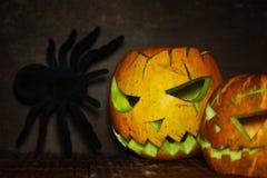 有蜘蛛的可怕南瓜灯笼在木头 免版税库存图片