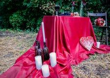 有蜡下落的瓶和在桌布的白色蜡烛 户外婚礼装饰 库存图片