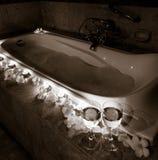 有蜡烛、葡萄酒杯花和夫妇的浪漫浴缸  库存照片