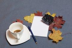 有蜡烛的伪造的金属烛台 有一个开放笔记薄和笔 一个杯子用未经同意的咖啡 y下落的秋叶  免版税库存图片