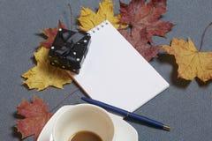 有蜡烛的伪造的金属烛台 有一个开放笔记薄和笔 一个杯子用未经同意的咖啡 y下落的秋叶  库存照片