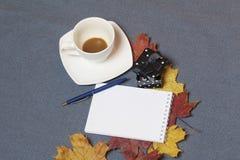 有蜡烛的伪造的金属烛台 有一个开放笔记薄和笔 一个杯子用未经同意的咖啡 y下落的秋叶  图库摄影
