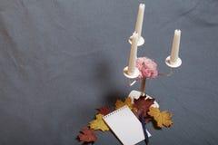 有蜡烛的伪造的金属烛台 有一个开放笔记薄和笔 驱散下落的秋叶黄色和红色  免版税库存图片