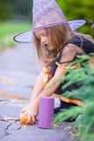 有蜡烛的可爱的小女孩佩带的巫婆服装在万圣夜秋天天 款待窍门 库存图片