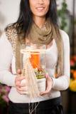 有蜡烛的女性卖花人在花店 图库摄影