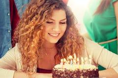 有蜡烛的愉快的妇女在党的生日蛋糕 库存图片