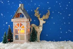有蜡烛的木老房子,在圣诞树旁边的白色鹿在雪和蓝色nackground 免版税库存照片