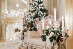 有蜡烛的枝形吊灯在前景 背景对光检查圣诞节构成黑暗的夜间新的s玩具年 与一个白色壁炉的经典公寓 库存图片