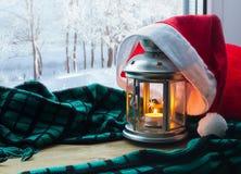 有蜡烛的灯笼和在窗台和冬天森林户外圣诞节和新年冬天背景的圣诞老人帽子 图库摄影