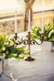 有蜡烛的葡萄酒古铜色烛台在与白色郁金香花束的桌上  图库摄影