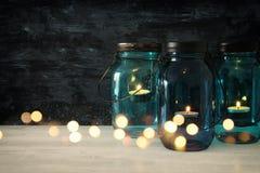 有蜡烛的葡萄酒装饰不可思议的金属螺盖玻璃瓶在木桌上点燃 免版税图库摄影