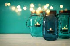 有蜡烛的葡萄酒装饰不可思议的金属螺盖玻璃瓶在木桌上点燃 免版税库存照片