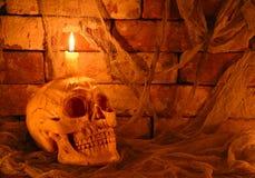 有蜡烛的蠕动的头骨在黑暗 库存图片