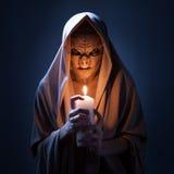 有蜡烛的魔术师在黑暗中 免版税库存照片