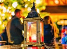 有蜡烛里面的灯笼的它在圣诞节市场中间生动了描述在冬天里加在拉脱维亚 免版税图库摄影