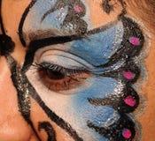 有蝴蝶表面油漆的妇女  库存照片