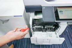 有螺丝刀在手中固定打印机的人 免版税图库摄影