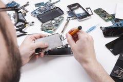 有螺丝刀的安装工拆卸的电话 免版税库存照片