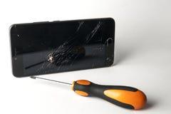 有螺丝刀的残破的智能手机 免版税库存图片