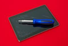 有螺丝刀的残破的片剂建议技术和小配件修理公司在保单下 免版税库存图片