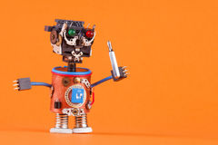 有螺丝刀的滑稽的机器人玩具 逗人喜爱的字符黑色塑料头,色的绿色红色注视灯,蓝色导线手 复制 库存图片