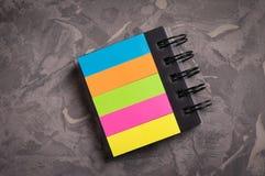 有螺旋和空白的笔记本上色了在老具体灰色水泥的页 库存照片