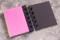 有螺旋和空白页桃红色颜色的被打开的笔记本在与拷贝空间的老具体灰色水泥 免版税库存图片