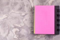 有螺旋和空白页桃红色颜色的被打开的笔记本在与拷贝空间的老具体灰色水泥 免版税库存照片