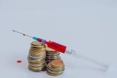 有血液的注射器在硬币血液 库存照片