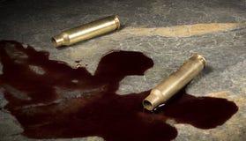 有血液的空的AR-15弹药在岩石 免版税库存图片