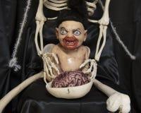 有血淋淋的嘴的妖怪婴孩在最基本的` s膝部 图库摄影