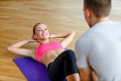有行使在健身房的男性教练员的微笑的妇女 免版税库存图片