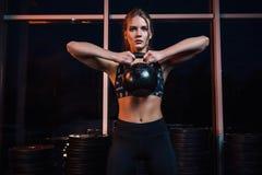 有行使crossfit的强健的身体的可爱的年轻运动员 做与水壶的运动服的妇女crossfit锻炼 免版税库存图片