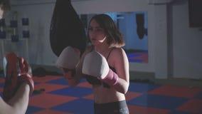 有行使kickboxing在4K的健身房的教练员的俏丽的女孩 股票录像