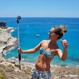 有行动照相机的少妇在地中海海岸 库存图片