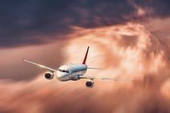 有行动迷离作用的飞机在大橙色云彩飞行 库存照片