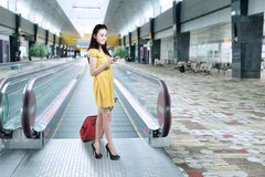 有行李和使用手机的女孩在机场 免版税库存照片