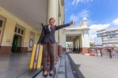 有行李的亚裔女商人要求在街道上的出租汽车在 免版税库存照片
